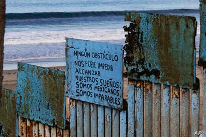 """A sign that reads in Spanish """"No obstacle can stop us from our dreams. We are Mexicans. We are unstoppable,"""" hangs on border structure from the Mexican side where the border meets the Pacific Ocean, Nov. 16, 2018."""