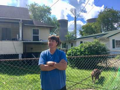 In this Aug. 23, 2018 photo, Andrea Maxey of Poca, West Virginia, speaks outside her home with the American Electric Power's John Amos coal-fired power plant is in the background across the Kanawha River in Winfield.