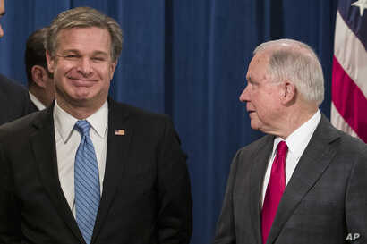 FBI Director Christopher Wray, left, smiles with Attorney General Jeff Sessions before a news conference about the arrest of Cesar Sayoc, 56, in the package bomb case, at the Department of Justice,  Oct. 26, 2018, in Washington.