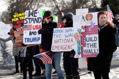 """Supporters hold signs at a Women for Trump """"Build the Wall"""" rally in Bloomfield Hills, Mich., Jan. 26, 2019."""