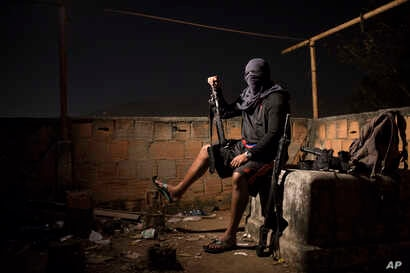 A drug gang leader poses for a photo, July 6, 2016, in a slum in Rio de Janeiro, Brazil. He told Associated Press journalists that drug dealers win the hearts and minds of locals by paying for food and medicine, providing a lifeline for many living i...