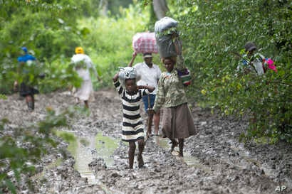 Villagers carry food for people taking care of their livestock in Tsholostho, about 200 kilometers north of Bulawayo, March 4, 2017.