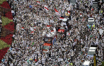 """Thousands of Muslims gather during a protest against Jakarta's minority Christian Governor Basuki """"Ahok"""" Tjahaja Purnama who is being prosecuted for blasphemy, at the National Monument in Jakarta, Indonesia, Friday, Dec. 2, 2016."""