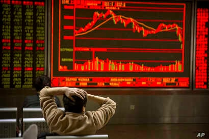 A Chinese investor monitors stock prices at a brokerage house in Beijing, Friday, Feb. 9, 2018. (AP Photo/Mark Schiefelbein)
