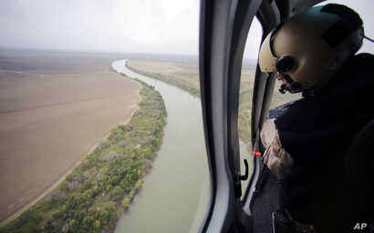 In this Feb. 24, 2015, aerial file photo, a U.S. Customs and Border Protection Air and Marine agent looks out along the Rio Grande on the Texas-Mexico border in Rio Grande City, Texas.