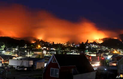 A wildfire approaches Chile's Dichato community, Jan. 30, 2017, where firefighters are working to keep the flames away from the estimated 800 homes.