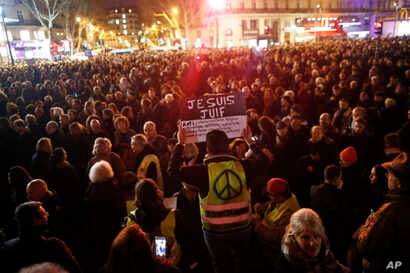 """A man wearing a yellow vest with a peace sign holds a placard reading """"I am a Jew,"""" during a gathering at the Place de la Republique to protest against rising anti-Semitism, in Paris, France, Feb. 19, 2019."""