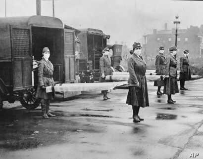 In this October 1918 photo made available by the Library of Congress, St. Louis Red Cross Motor Corps personnel wear masks as they hold stretchers next to ambulances in preparation for victims of the influenza epidemic.