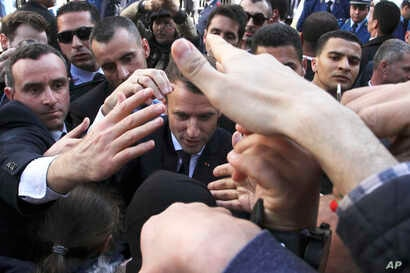 French President Emmanuel Macron is protected by security members as he meets residents in Algiers, Wednesday, Dec.6, 2017. Macron is traveling to Algeria for a one-day working visit aimed at boosting the security and economic cooperation between the...