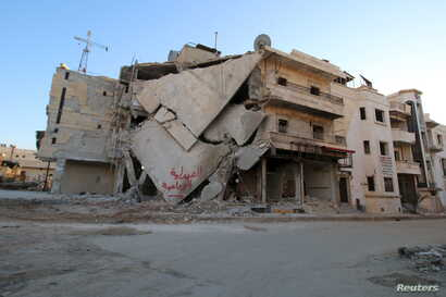 """A damaged building is seen in Hraytan city, about 10 kilometers away from the towns of Nubul and Zahraa, Northern Aleppo countryside, Syria, Feb. 3, 2016. The text on the building reads in Arabic: """"Agricultural pharmacy."""""""