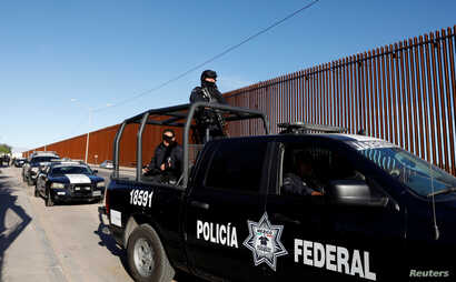 Mexican federal police guard the wall during the visit of U.S. President Donald Trump to Calexico, California, in Mexicali, Mexico,  April 5, 2019.