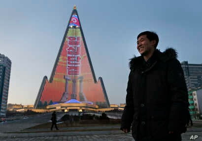 Light designer Kim Yong Il smiles, Dec. 20, 2018, as his light show on the facade of the Ryugyong Hotel is seen in the background. For several hours each night, the building that doesn't have electricity inside becomes the backdrop of a massive ligh...