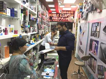 Owner of a shop selling mobiles and accessories in a posh New Delhi market, Manu Talwar (standing with register) says his sales have dropped by 30 per cent in the last year after India imposed a currency ban.