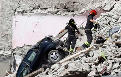 Rescuers make their way through destroyed houses following Wednesday's earthquake in Pescara Del Tronto, Italy, Aug. 25, 2016.