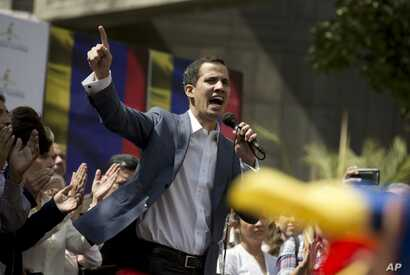 FILE - Juan Guaido, president of the Venezuelan National Assembly delivers a speech during a public session with opposition members, at a street in Caracas, Venezuela, Jan. 11, 2019.