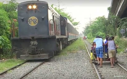 Commuters ride wooden carts pushed along the railroad tracks to avoid Manila's infamous traffic gridlock.