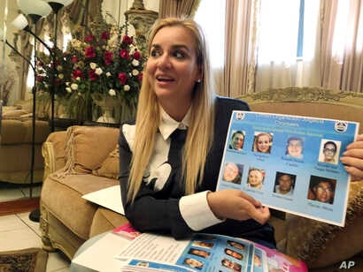 FILE - Darling Perez shows a copy of a Nicaraguan government wanted poster in which she is listed, during an interview in Miami, Oct. 15, 2018.