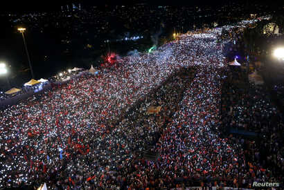 People gather for a ceremony marking the first anniversary of an attempted coup at the Bosporus Bridge in Istanbul, Turkey, July 15, 2017.