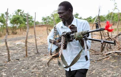 An opposition fighter walks with his weapon on which is tied a red ribbon, signifying danger as a warning to government forces and a willingness to shed blood, according to an opposition spokesman, in Akobo town, one of the last rebel-held stronghold
