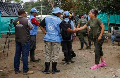 A United Nation observer shakes hands with a rebel of Revolutionary Armed Forces of Colombia (FARC) before a meeting in La Carmelita near Puerto Asis in Colombia's southwestern state of Putumayo, March 1, 2017. Thousands of leftist rebels are taking