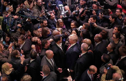 FILE - Then-Republican presidential candidate Donald Trump, center right, says goodbye to Dr. Darrell Scott, foreground left center, the senior pastor of New Spirit Revival Ministries in Cleveland Heights, Ohio, surrounded by media in the lobby of Tr...
