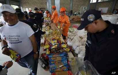 Venezuelan volunteers, Colombian firefighters and rescue workers prepare USAID humanitarian aid for storage at a warehouse next to the Tienditas International Bridge, near Cucuta, Colombia, on the border with Venezuela, Feb. 8, 2019.