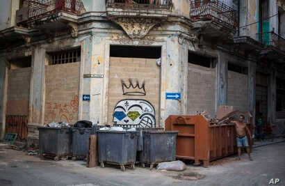 FILE - A man throws garbage into a container in Old Havana, Cuba, Oct. 22, 2018.