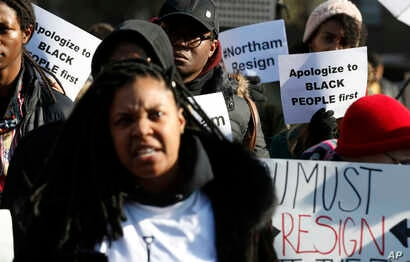 Demonstrators hold signs and chant outside the Governor's Mansion at the Capitol in Richmond, Virginia, Feb. 2, 2019. The protesters are calling for the resignation of Virginia Gov. Ralph Northam after a decades-old photo with a blackface is unearthe...