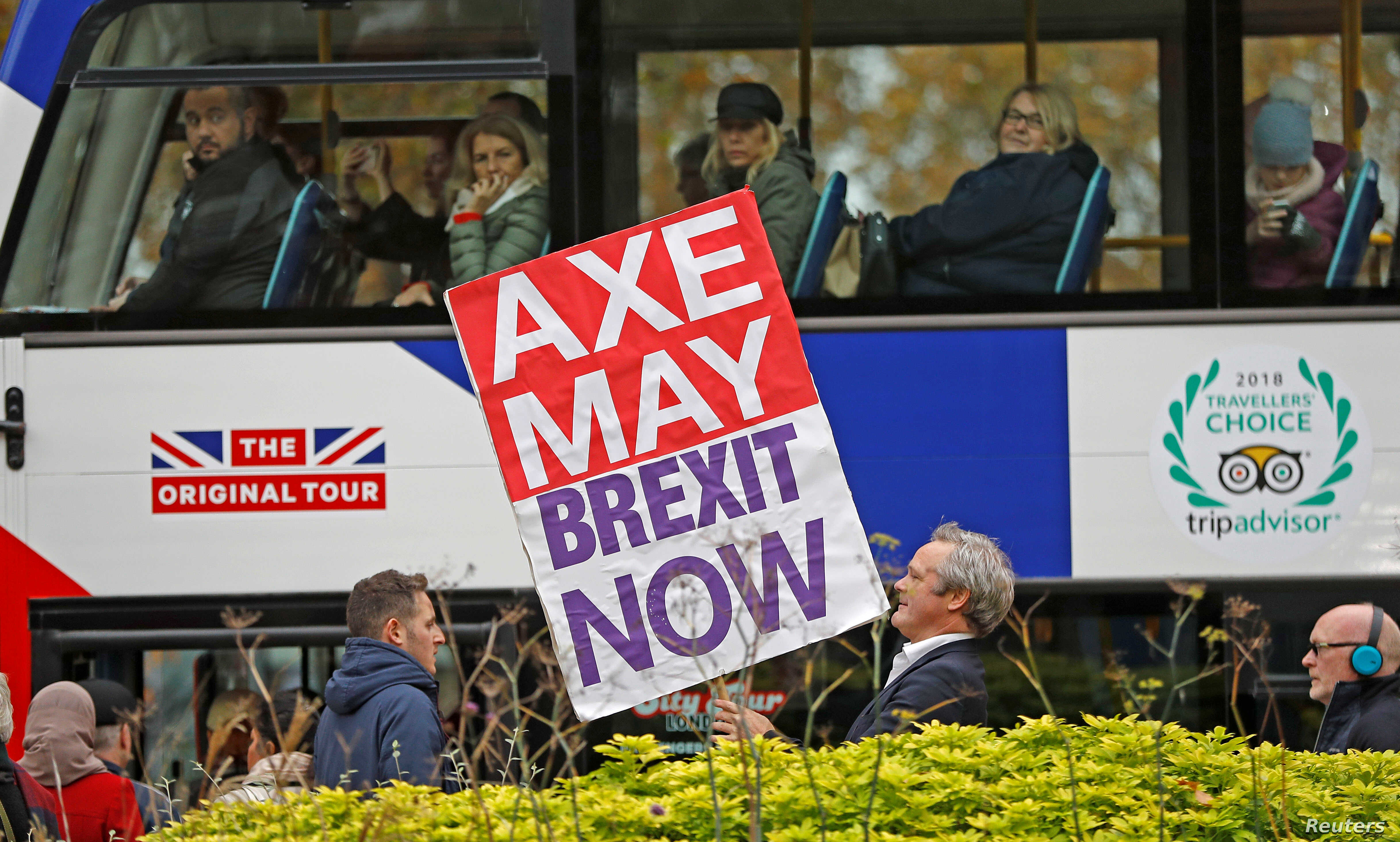 A pro-Brexit campaigner holds a placard as a tourist bus passes by in Westminster London, Britain, Nov. 16, 2018.