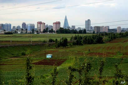 FILE - This June 15, 2018, file photo shows the Pyongyang skyline where the 105-story pyramid-shaped Ryugyong Hotel towers over residential apartments in the background of some agricultural land on the outskirts of Pyongyang, North Korea.