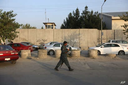 An Afghan security official patrols after an attack on the American University of Afghanistan in Kabul, Afghanistan, Aug. 25, 2016.