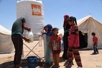 Displaced Iraqis from Fallujah fill their jerrycans with water supplied by NRC at Amariyat Al Fallujah displacement camp, June 11, 2016. Photo: Karl Schembri/NRC