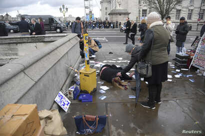 A woman lies injured after a shooting incident on Westminster Bridge in London, March 22, 2017.