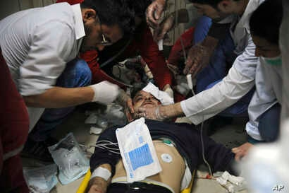 This photo released by the Syrian official news agency SANA shows a man receiving treatment at a hospital in Damascus, Syria, April. 7, 2018. State TV said Army of Islam fighters pelted several neighborhoods in Damascus with mortar shells, killing si...