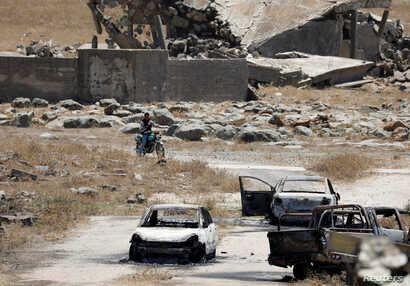 Burnt cars are seen in Quneitra, Syria, July 27, 2018.