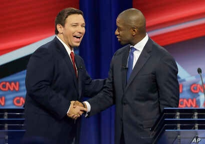 Florida Republican gubernatorial candidate Ron DeSantis, left, shakes hands with Democratic gubernatorial candidate Andrew Gillum after a CNN debate, Sunday, Oct. 21, 2018, in Tampa, Florida.