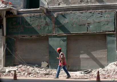 A worker walks past the Hinhayat watch shop, which was established in 1907 by a Bulgarian craftsman, that is being removed in the Maspero neighborhood of Cairo, Egypt, Aug. 11, 2018.