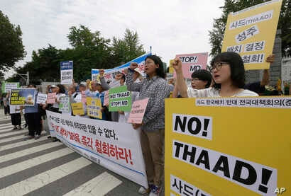 Protesters shout slogans during a rally to denounce deploying the Terminal High-Altitude Area Defense, or THAAD, in front of the Defense Ministry in Seoul, South Korea, Wednesday, July 13, 2016.