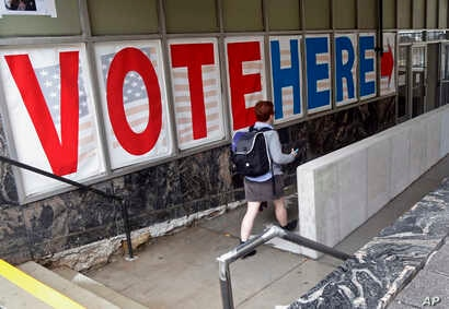 FILE - A voter passes a large sign before voting in Minneapolis.
