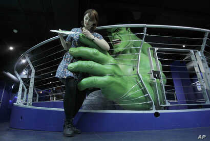 Madame Tussauds employee Marie Chandler poses for photographers beside a waxwork of The Hulk during the launch of the Marvel Super Heroes 4D exhibit at the Madame Tussauds waxworks in London, June 2, 2010.