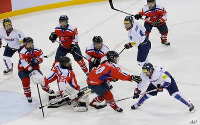 FILE - South Korea's Lee Eun-ji, bottom right, scores a goal as North Korea's Kim Kum Bok, bottom second right, tries to block the puck during their IIHF Ice Hockey Women's World Championship Division II Group A game in Gangneung, South Korea, April ...