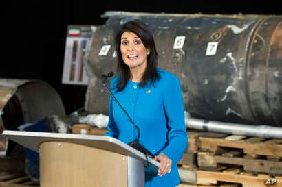 """U.S. Ambassador to the U.N. Nikki Haley speaks in front of recovered segments of an Iranian rocket during a press briefing at Joint Base Anacostia-Bolling, Dec. 14, 2017, in Washington. Haley says """"undeniable"""" evidence proves Iran is violating inter..."""