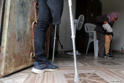 Palestinian woman Nazeeha Qudeih, 38, who, according to medics, lost her right leg after she was shot by Israeli forces during a protest at the Israel-Gaza border, puts on her artificial limb as her brother Suhaib, 33, who also lost a leg in the prot...