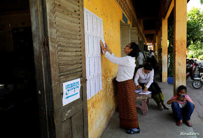 An election worker posts a voter list outside a polling booth located at a school in Phnom Penh, Cambodia, July 28, 2018.
