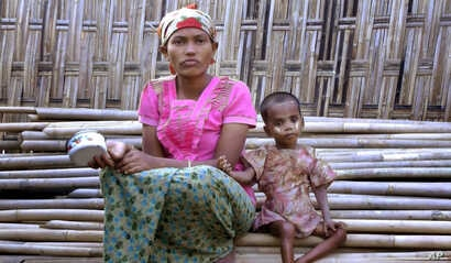 In this March 17, 2017, image made from video, Rosmaida Bibi, right, who suffers from severe malnutrition, sits with her 20-year old mother Hamida Begum outside their makeshift shelter at the Dar Paing camp, north of Sittwe, Rakhine State, Myanmar.