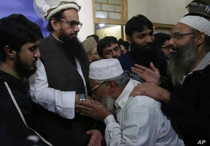 Supporters of Hafiz Saeed, second from left, head of the Pakistani religious party, Jamaat-ud-Dawa, kiss his hands as he arrived at a mosque in Lahore, Pakistan, Nov. 24, 2017.