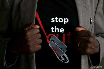 """FILE - A man's T-shirt reads """"Stop the Cut"""" referring to Female Genital Mutilation during a social event advocating against such harmful practices at the Imbirikani Girls High School in Imbirikani, Kenya, April 21, 2016."""