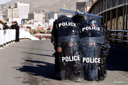 U.S. Custom and Border Protection agents with full riot gear take part in a drill to protect the crossing gates against people who want to cross the border illegally on the international bridge between Mexico and the U.S., in Ciudad Juarez, Mexico Oc...