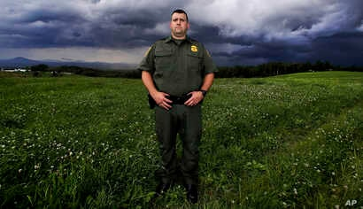 In this July 10, 2018 photo,  U.S. Border Patrol Agent Richard Ross, poses for a portrait in a field where people entering the United States illegally from Canada have been apprehended, in Derby Line, Vt.