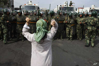FILE - In this July 7, 2009 photo, a Uigher woman demands the return of members from her community before a group of paramilitary police officers when journalists visited the area in Urumqi in western China's Xinjiang province.